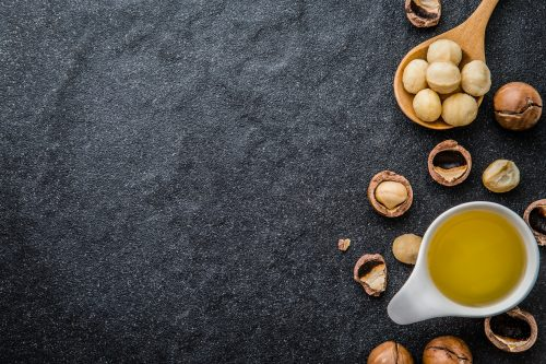 The Macadamia Nut Oil and peeled macadamia nut  on black stone , use for Healthy Skin and Hair and Natural Healing Oil Treatment , overhead and top view